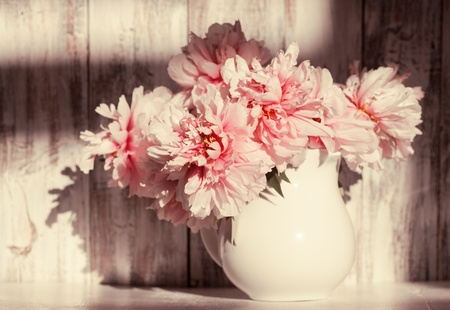 Still life with peonies over shabby wooden wall photo