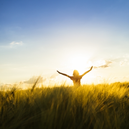 outstretched hand: Teenage girl enjoy with sunshine in wheat field Stock Photo