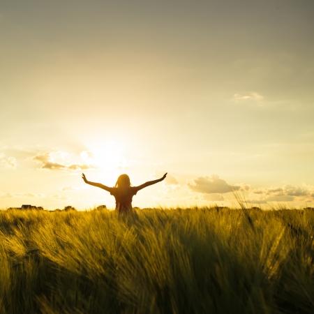 Teenager-Mädchen genießen mit Sonne im Abendrot