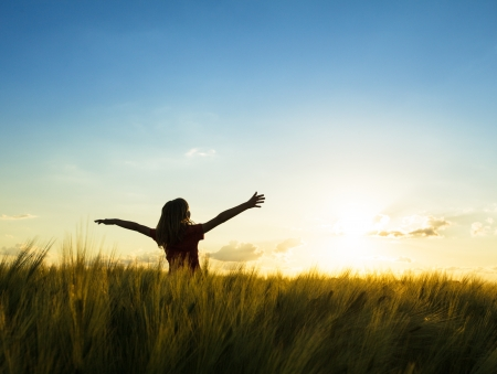 field sunset: Teenage girl enjoy with sunshine in wheat field Stock Photo