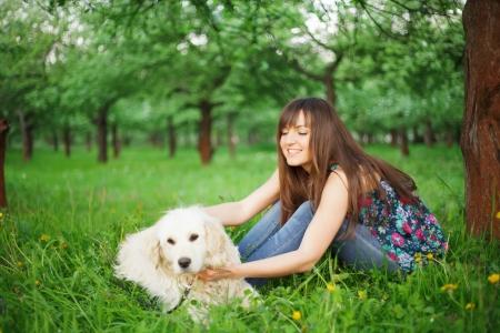 La mujer juega con su perro - perro perdiguero de oro en el parque Foto de archivo