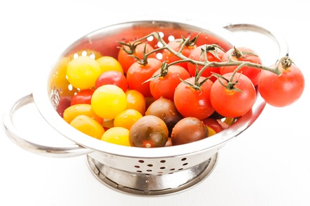 Red, yellow and black  cherry tomatoes in colander on white photo