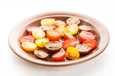 Various types of cherry tomatoes on the plate. Tomato salad on white table photo