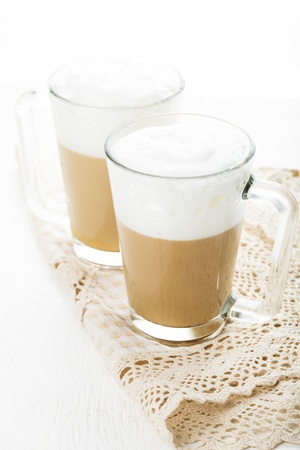 Coffee latte in glass mugs on white table photo