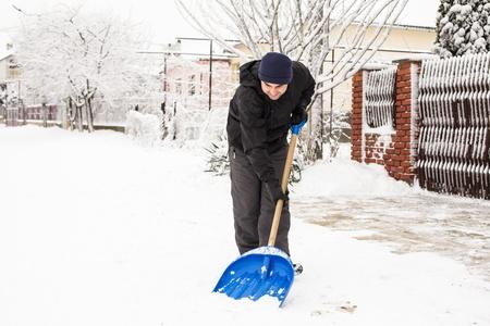 Hombre joven que quitar la nieve cerca de la casa de las afueras