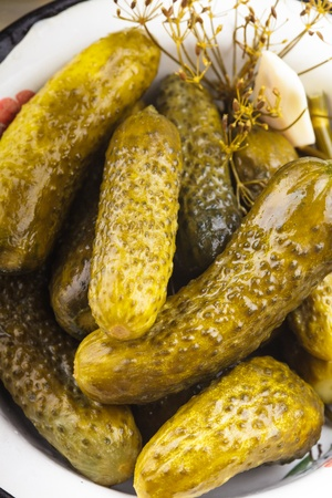 gherkins: salted cucumber in the metal bowl on the table