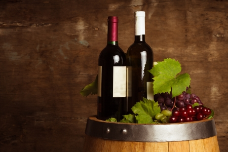 Bottles of wine on the oak barrel over old shabby wooden background photo