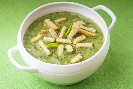Fresh green spinach cream soup with croutons in a bowl photo