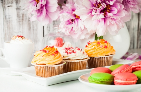 Lovely cakes and macaroons with coffee and flowers photo
