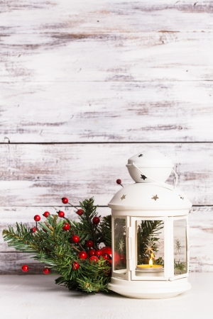 Cristmas lantern with fir and berries over shabby wooden background photo