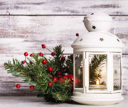 Cristmas lantern with fir and berries over shabby wooden background