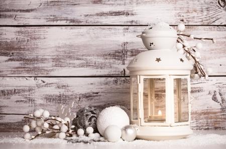 Cristmas linterna con decoraciones y nieve sobre el fondo blanco de madera en mal estado