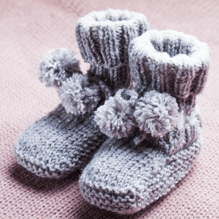 Knitted wool baby booties with pompons close up photo