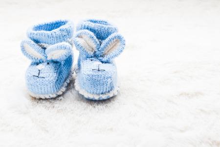 Gebreide blauwe baby booties met konijn snuit voor kleine jongen Stockfoto