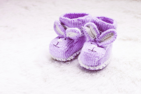 muzzle: Knitted purple baby booties with rabbit muzzle over fur