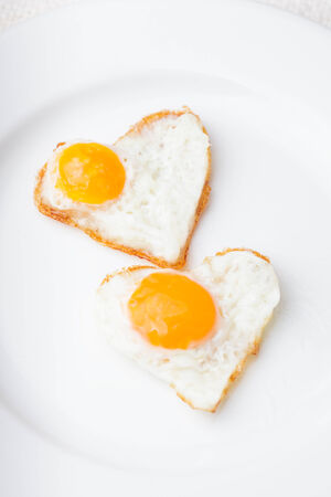 Heart shape fried eggs on the white plate photo