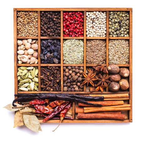 Different types of spices in wooden box isolated on white Stock Photo