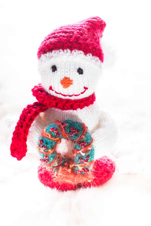Knitted snowman with christmas wreath on white snow photo