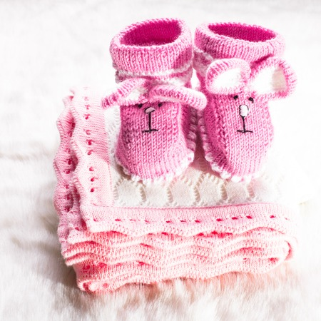 Knitted pink baby booties and blanket for little girl photo
