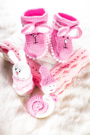 Knitted pink baby booties, toys, blanket for little girl photo