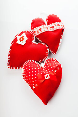 Sewed handmade red hearts on a white background photo