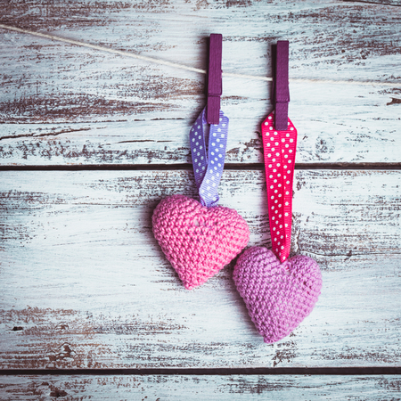 Crochet valentine hearts handing on the rope. Valentines day greeting card. Love concept photo