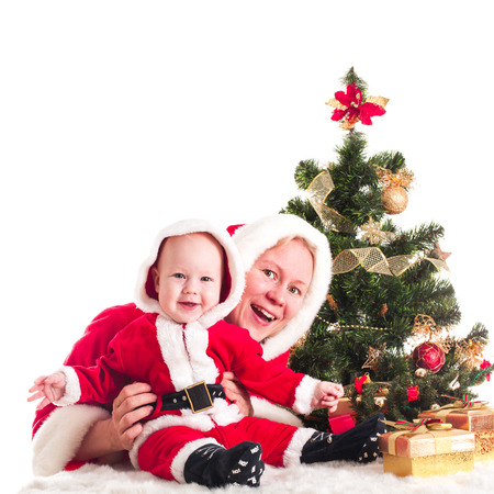 Christmas baby and mom under the fir tree isolated photo