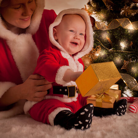 Christmas baby and mom open gifts under the fir tree photo