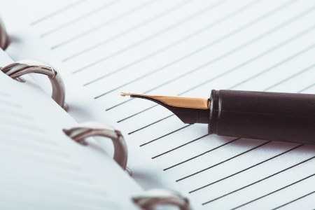 college ruled: Metal feather pen on the ruled paper in the notebook Stock Photo