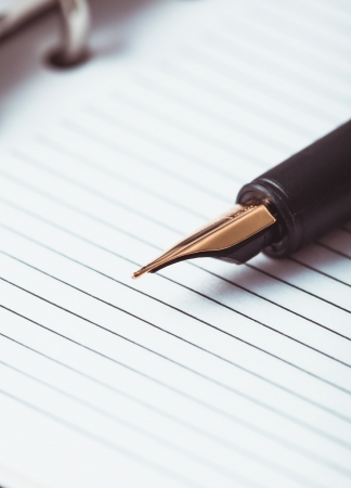 Metal feather pen on the ruled paper in the notebook photo