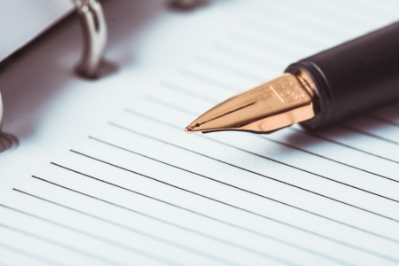 ruled paper: Metal feather pen on the ruled paper in the notebook Stock Photo