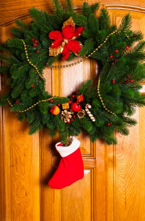 Christmas wreath with red sock on the door photo