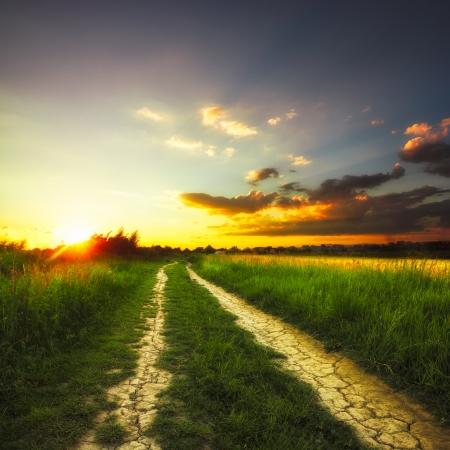Pad in het veld en zonsondergang. Landelijk landschap