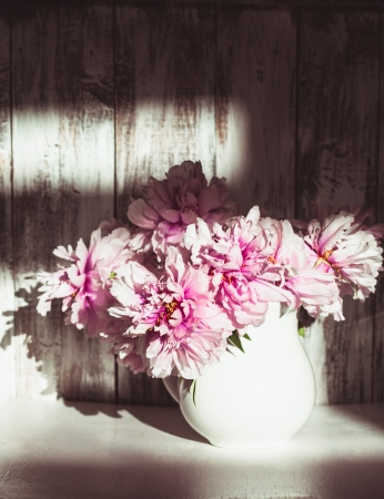 Still life with peonies over shabby wooden wall with sunlight from window photo