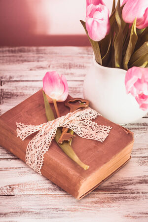 Memo still life with book, key, vintage lace and pink tulips photo