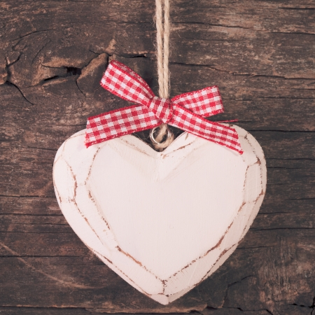 White carved heart over old wooden  photo