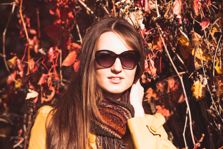 Woman is walking in autumnal park in glasses photo