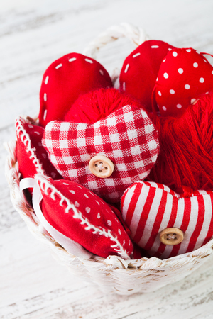Valentine decorations: textile red hearts in white basket on the shabby table photo