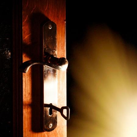 Offene Tür mit Schlüssel in den dunklen Raum mit Licht Lizenzfreie Bilder