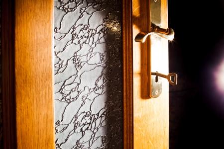 Open door with key into the dark room with light photo