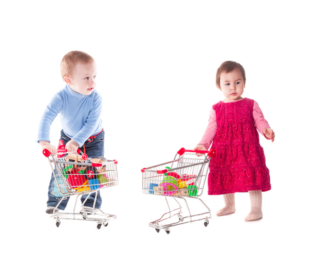 playing the market: Boy and girl play with shopping trolley and toys, isolated on white