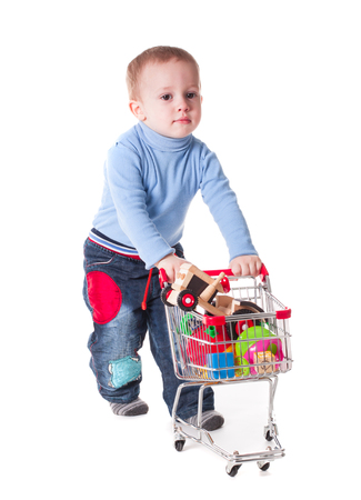 playing the market: Boy plays with shopping trolley and toys, isolated on white Stock Photo