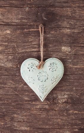 Metal heart on the shabby wooden background photo