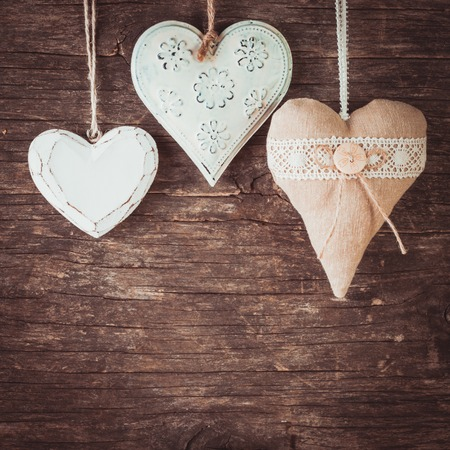 Metal, textile and wooden heart on the old natural background