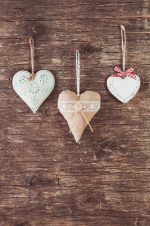 Metal, textile and wooden heart on the old natural background photo