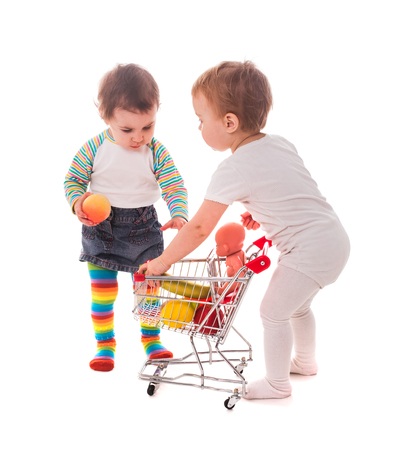 playing the market: Little girls play with shopping trolley and doll. Grocery store playing