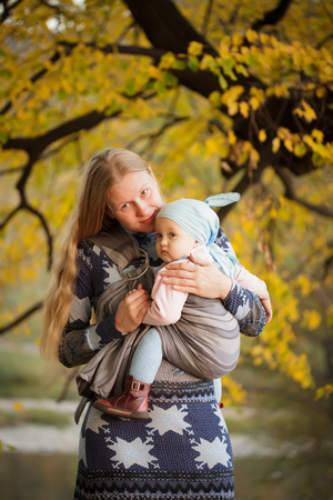 Mother walking with  baby in sling in the park photo