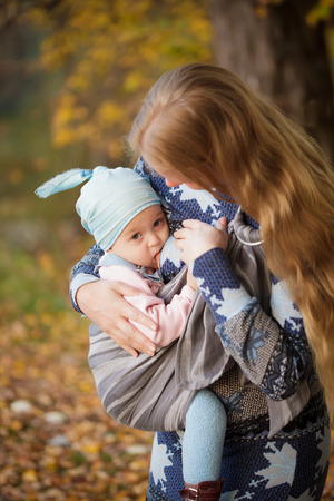 Mother walking with child outdoor, baby nursing in sling photo