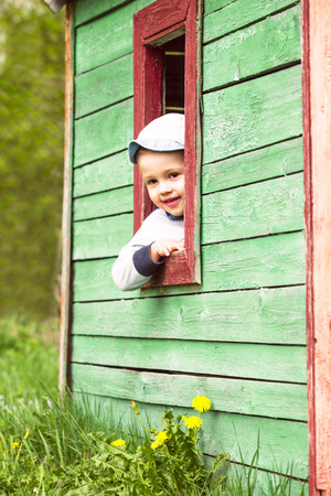 Boy plays in little  toy wooden house outdoor