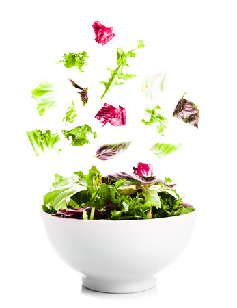 Falling salad with green leaves in a bowl on the white photo